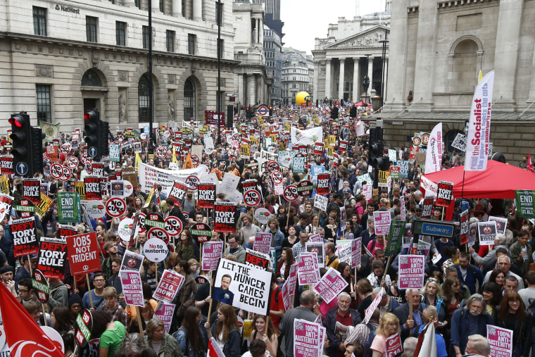 Image: Demonstrators with placards crowd the area around the Bank of England as they protest austerity measures in London, Saturday.