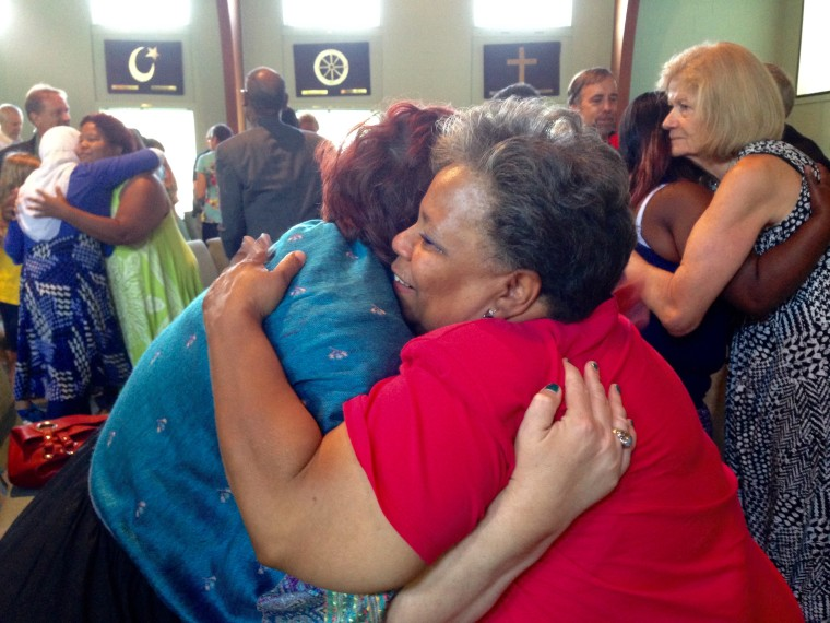 Local artist and unity church board president Cookie Washington, right, hugs a friend after an interdenominational prayer service for healing at Unity church in North Charleston Saturday morning.