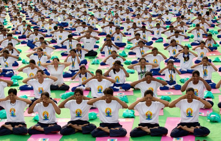 Image: Indians perform yoga on Rajpath, in New Delhi