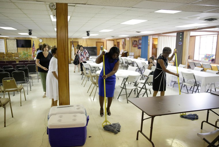 Image: Parishioners clean a room in the basement