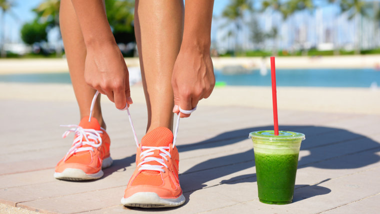 Woman with green juice tying sneakers