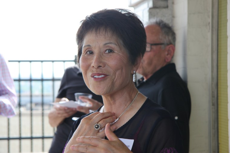 """Dr. Sook Wilkinson, Co-Editor with Victor Jew of """"Asian Americans in Michigan—Voices from the Midwest"""" and former chair of the Michigan Asian Pacific American Affairs Commission, at the Wayne State University Press book launch party last week in Detroit with book cover"""