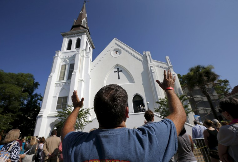 Image: Robin Goolfby raises his arms as church-goers who cannot fit into the Emanuel African Methodist Episcopal Church stand in the street during a service in Charleston