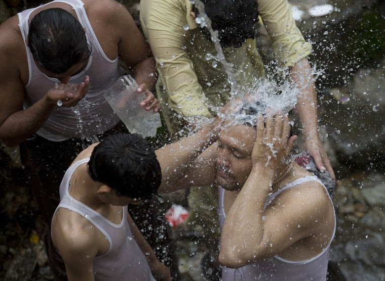 Image: Pakistanis cool themselves Tuesday under a broken water pipe in Islamabad as temperatures increase during Ramadan