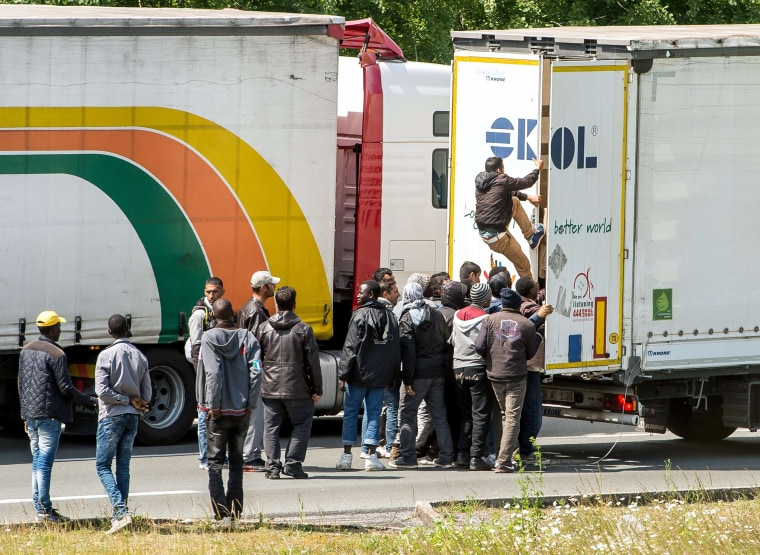 Image: Migrants climb in a truck heading to the Eurotunnel in Calais in northern France