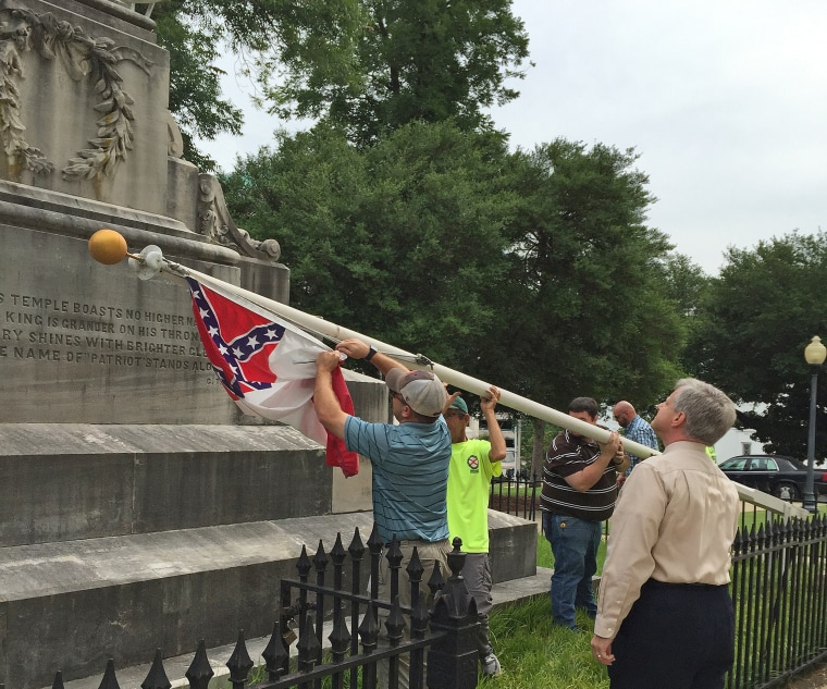 State workers take down a Confederate national flag on the grounds of the Capitol on June 24 in Montgomery, Ala.