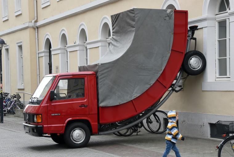 A child walks past the work 'Truck' by Austrian artist Erwin Wurm in Karlsruhe, Germany, on Sunday.