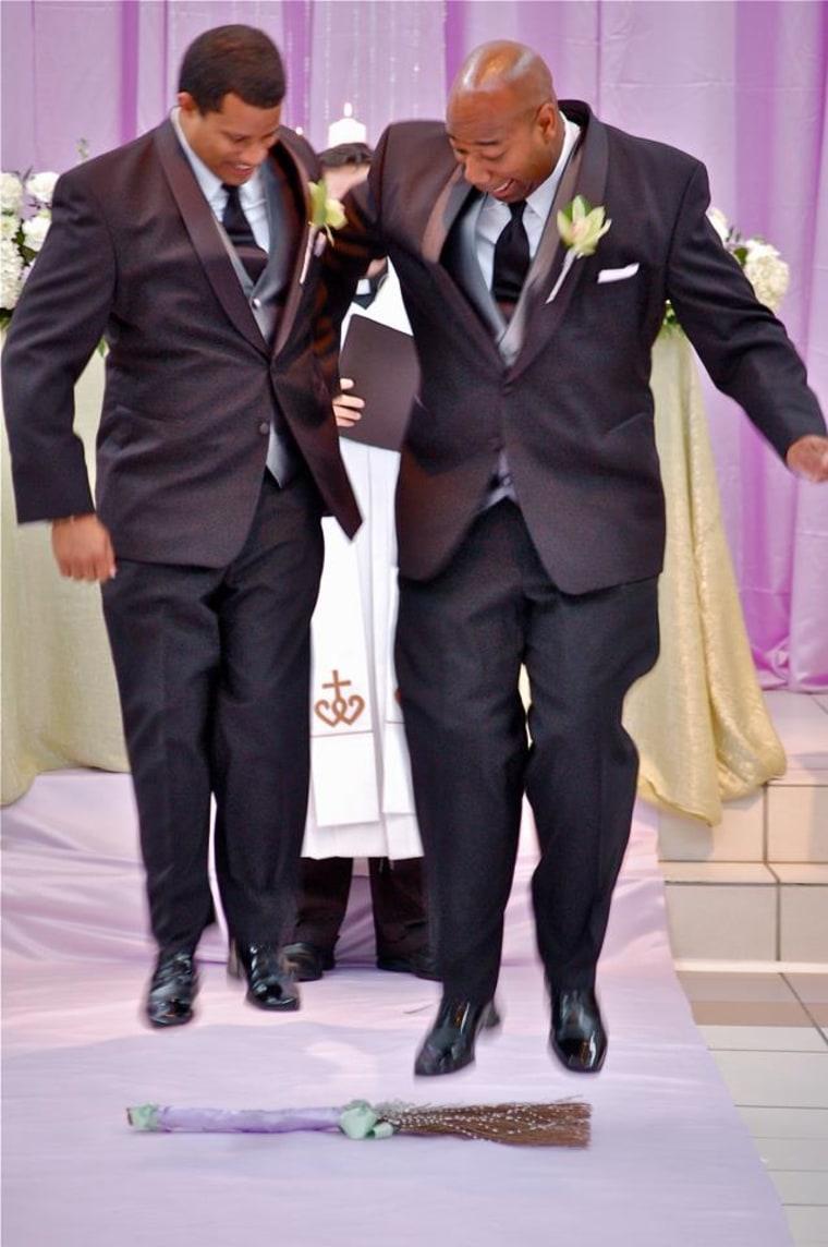 College sweethearts Kareem Murphy and Rev. Dewayne Davis jump the broom at their wedding.