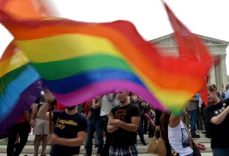 People wave a multicolored flag outside the Supreme Court in Washington, DC on June 26, 2015 after its historic decision on gay marriage. The US Supreme Court ruled Friday that gay marriage is a nationwide right, a landmark decision in one of the most keenly awaited announcements in decades and sparking scenes of jubilation. The nation's highest court, in a narrow 5-4 decision, said the US Constitution requires all states to carry out and recognize marriage between people of the same sex. AFP PHOTO/ MLADEN ANTONOVMLADEN ANTONOV/AFP/Getty Images