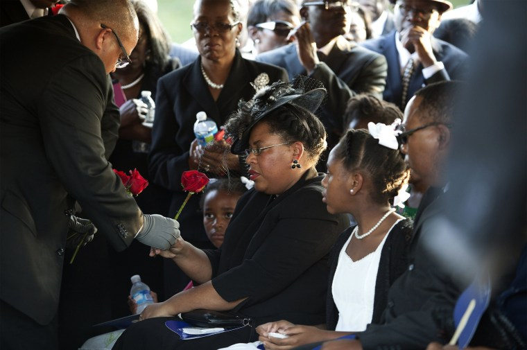 Image: Jennifer Pinckney accepts a rose at the burial of her husband Reverend Clementa Pinckney at the St James AME Church Cemetery in Marion, South Carolina