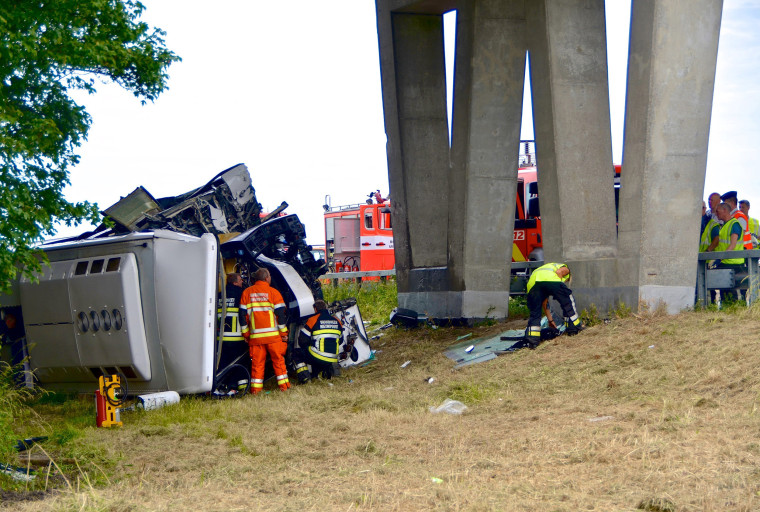 Image: Rescuers stand next to a British bus, transporting 34 children and which overturned and crashed on a motorway near the city of Middelkerke