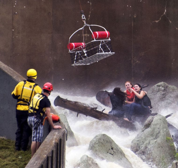 A rescue basket lowered from Maryland State Police helicopter Trooper 3 nears three girls trapped on rocks in the swift current in the spillway of the Lake Linganore dam Saturday evening.