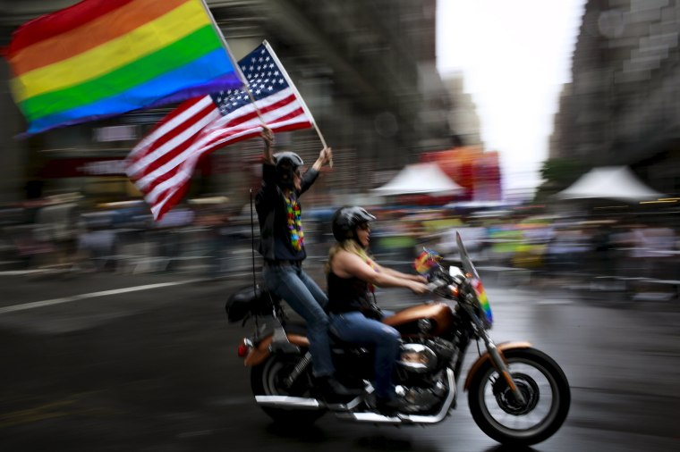 Image: Couple carry an American flag and a rainbow flag during the annual Gay Pride parade in New York