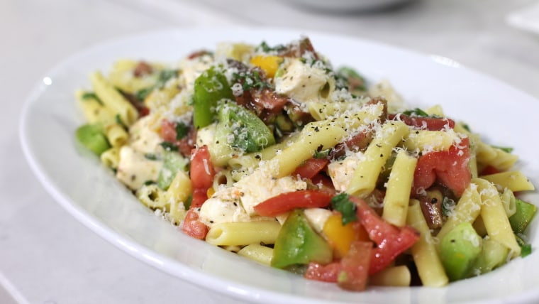 Penne pasta with heirloom tomatoes, grated parmesan cheese, basil and other ingredients.