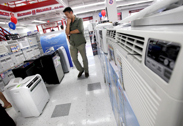 A man looks at air conditioners for sale at a P.C. Richard & Son store, in New York,  Sunday, July 1, 2012.