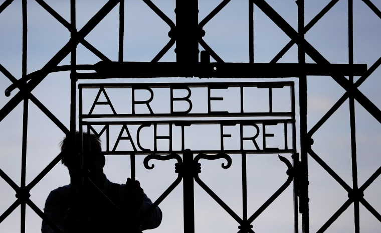 """Image: A blacksmith prepares a replica of the Dachau Nazi concentration camp gate, with the writing """"Arbeit macht frei"""" (Work Sets you Free) at the main entrance, in April 2015."""