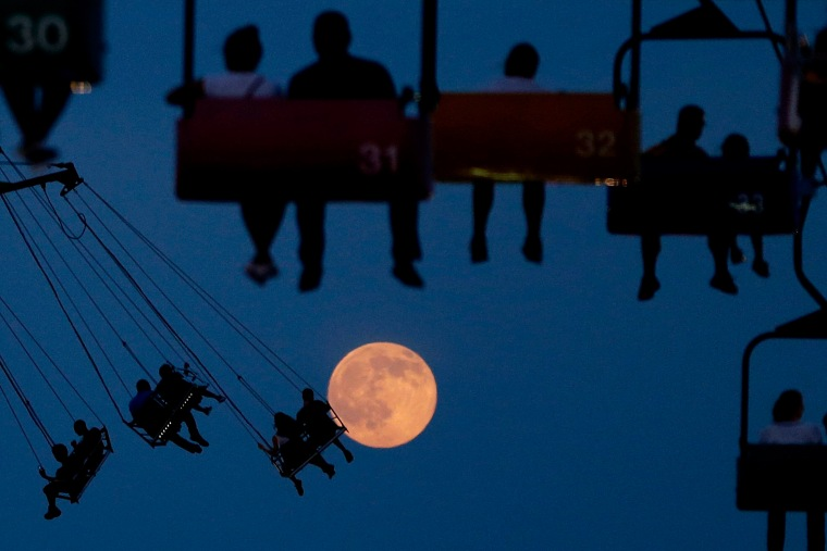 Image: The moon rises as people sit on rides at the State Fair Meadowlands