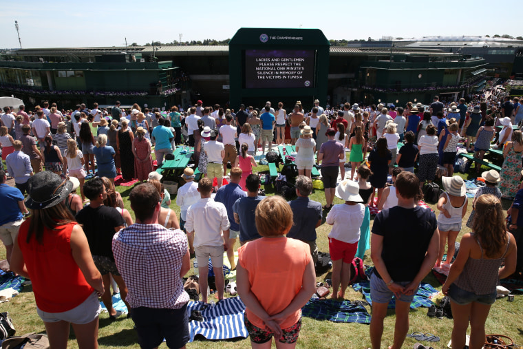 Image: Spectators stand on Murray Mount (Henman Hill) for a minute's silence