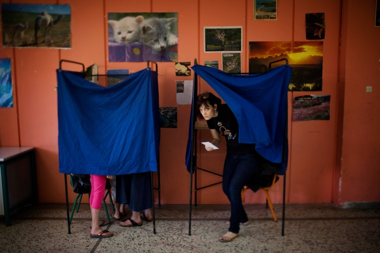 Image: A woman leaves a cabin before casting her vote at a polling station in Athens