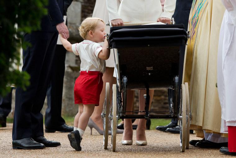 Image: Britain's Prince George gets up on tiptoes to peek into the pram of Princess Charlotte