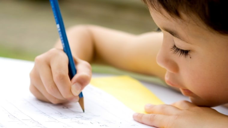 Little boy writing a letter