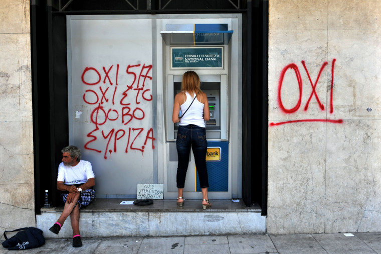 """Image: A woman withdraws money from an ATM machine next to a beggar and a graffiti reading"""" No to fear"""" in Thessaloniki on July 6, 2015"""