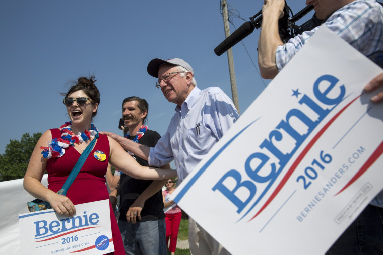Image: Democratic presidential hopeful Sen. Bernie Sanders takes photos with supporters during the Independence Day Parade in Creston, Iowa