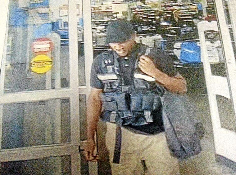 In this July 4, 2015 frame from surveillance video provided by the Bristow Police Department, a man leaves with more than $75,000 from a Wal-Mart after disguising himself as an armored truck driver in Bristow, Okla. Authorities say the suspect walked to the cash office, signed for the deposit and walked out of the store.