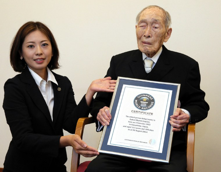 In this file picture taken on August 20, 2014, 111-year-old Japanese man Sakari Momoi receives a certificate naming him as the world's oldest man by the Guinness World Records at a hospital in Tokyo. Momoi died in Japan at age 112.