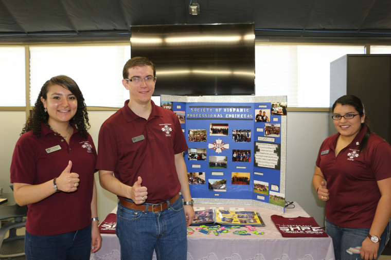 """A group of Texas A&M engineering students flash the """"gig 'em""""  - thumbs up - school sign at the main campus, in front of a Society of Hispanic Professional Engineers display."""