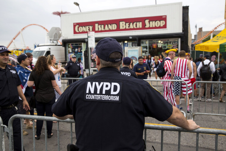 Image: A New York Police Officer watches crowds before the annual Fourth of July 2015 Nathan's Famous Hot Dog Eating Contest in Brooklyn, New York