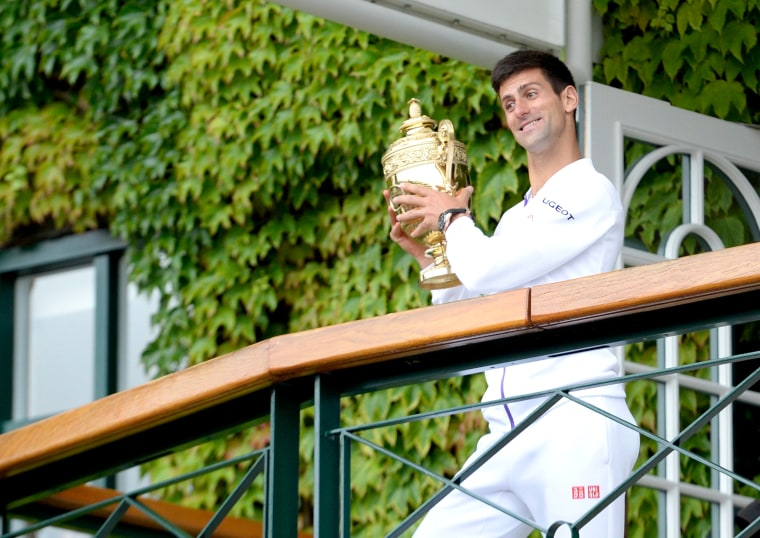 Novak Djokovic holds the championship trophy after beating Federer in the men's final of the Wimbledon Tennis Championships.