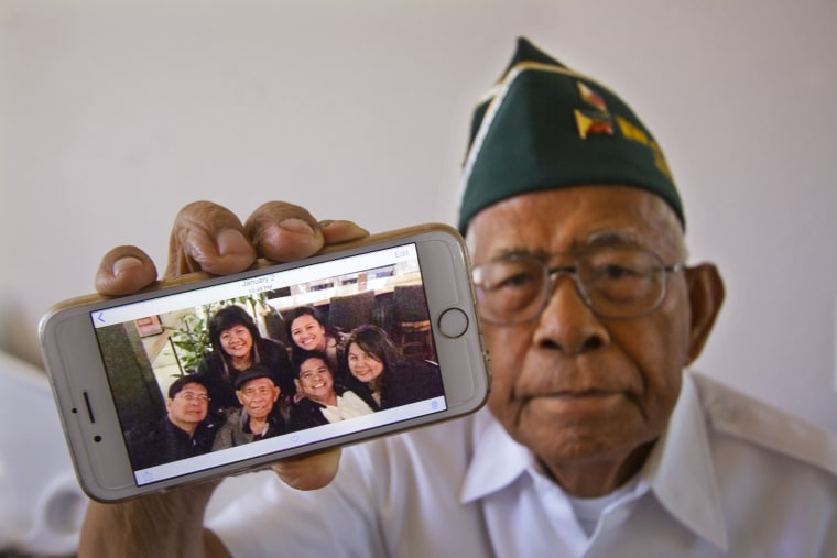 In this March 27, 2015 photo, Filipino World War II veteran Artemio Caleda holds up a family photo at his home in Ewa Beach, Hawaii. Although the shrapnel scar Caleda picked up picked up during World War II is now seven decades old and faint, it serves as a stinging reminder that Caleda is still fighting a battle: to have his three grown sons join him in the United States.