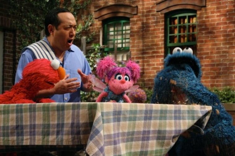 Alan Muraoka with Elmo, Abby, and Cookie.