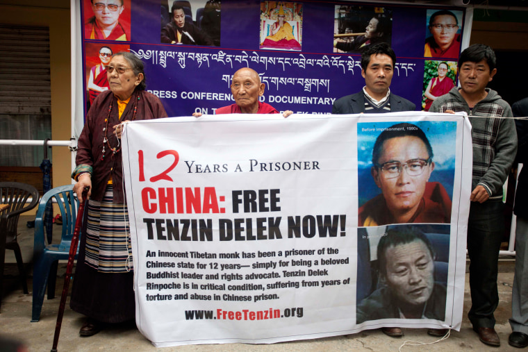 Image: Exiled Tibetans hold a banner in Dharmsala, India