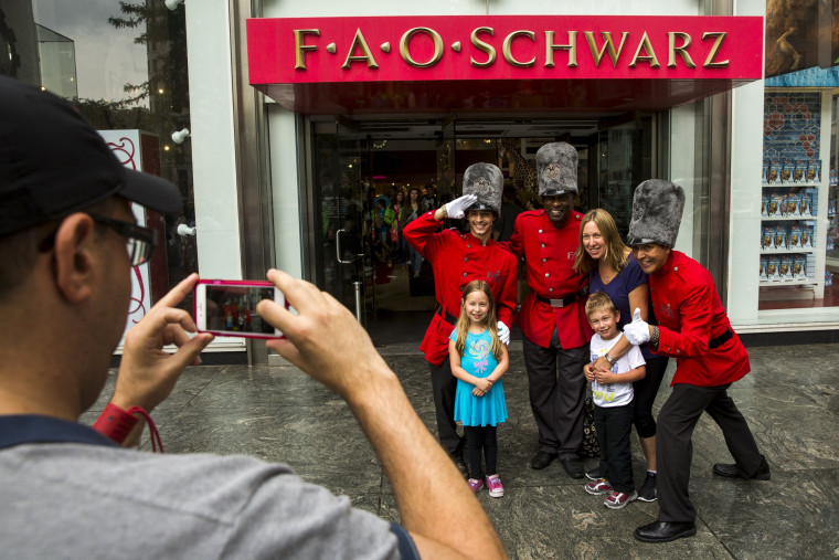 Image: Tourists pose with costumed employees outside of the toy store FAO Schwarz on the last day that the store will be open in New York