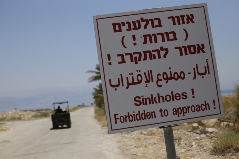 A sign warns of sinkholes at the closed Mineral Beach resort on the Israeli side of the Dead Sea.