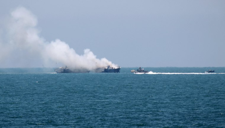 Image: Smokes rises from an Egyptian coastguard vessel on the coast of northern Sinai, as seen from the border of southern Gaza Strip with Egypt