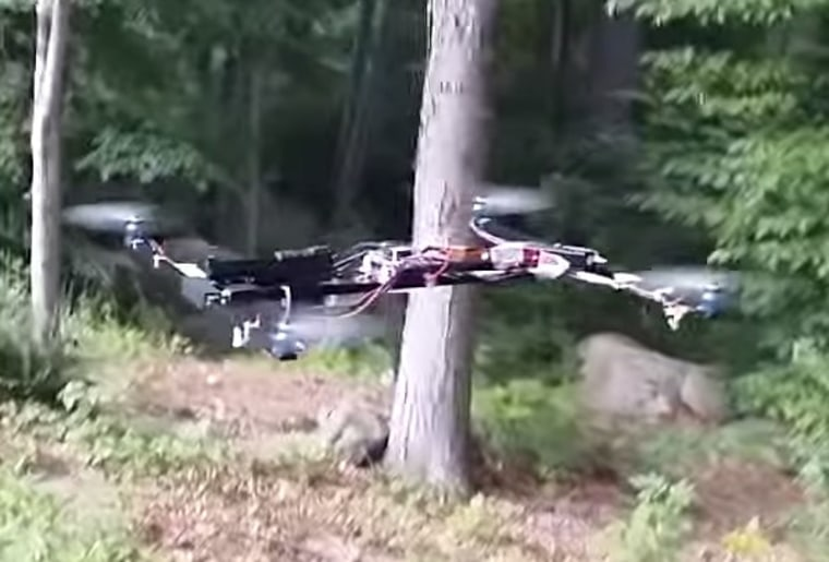 Image: YouTube screenshot shows a drone flying in a wooded area with a gun strapped to it