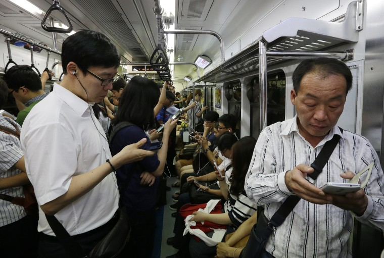 Image: Passengers use their smartphones on a subway train in Seoul, South Korea.