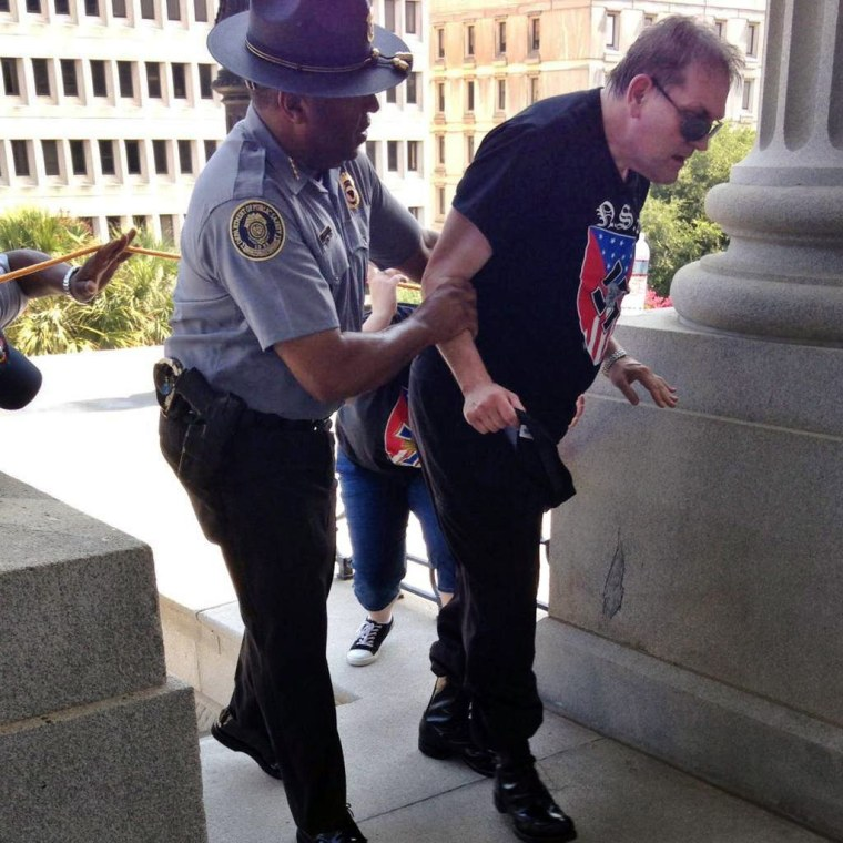 Image: Police officer Leroy Smith helps a man wearing National Socialist Movement attire amid intense heat at Saturday's rallies in Columbia, S.C.