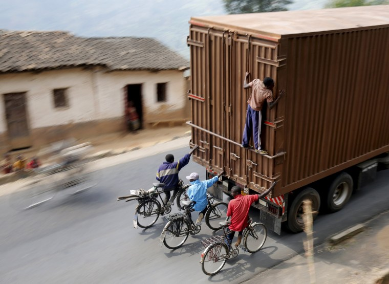 Image: Cylists hang to the back of a truck outside the capital Bujumbura as the country awaits next week's presidential elections