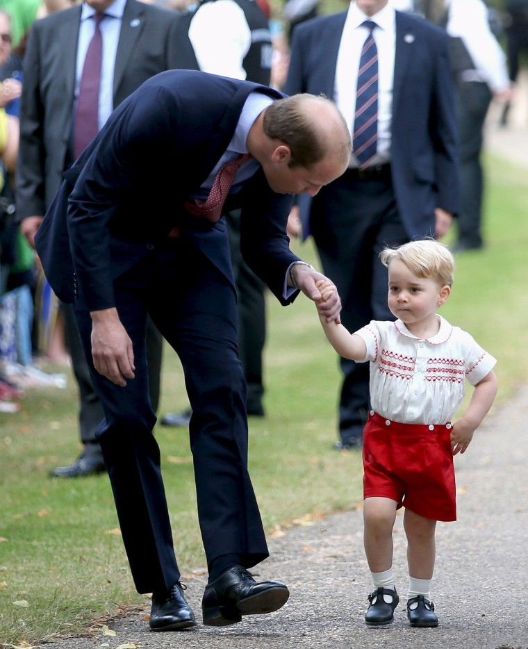 Prince William, Duke of Cambridge speaks with Prince George of Cambridge as they arrive at the Church of St Mary Magdalene on the Sandringham Estate for the Christening of Princess Charlotte of Cambridge
