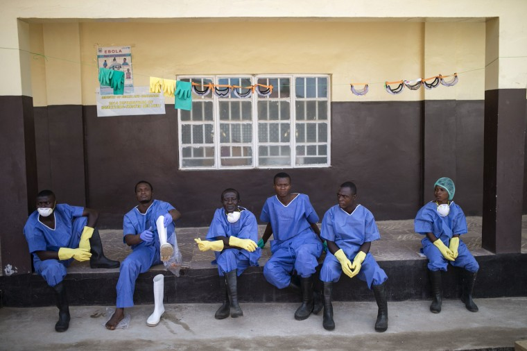 Image: Health workers rest outside a quarantine zone at a Red Cross facility in the town of Koidu