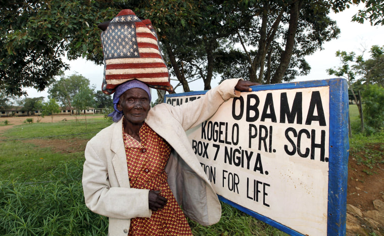 Image: Rosa Anyango poses for a photograph as she carries a bag with the colors of the U.S. flag as she walks from the market near the ancestral home of U.S. President Barack Obama in Nyangoma village in Kogelo