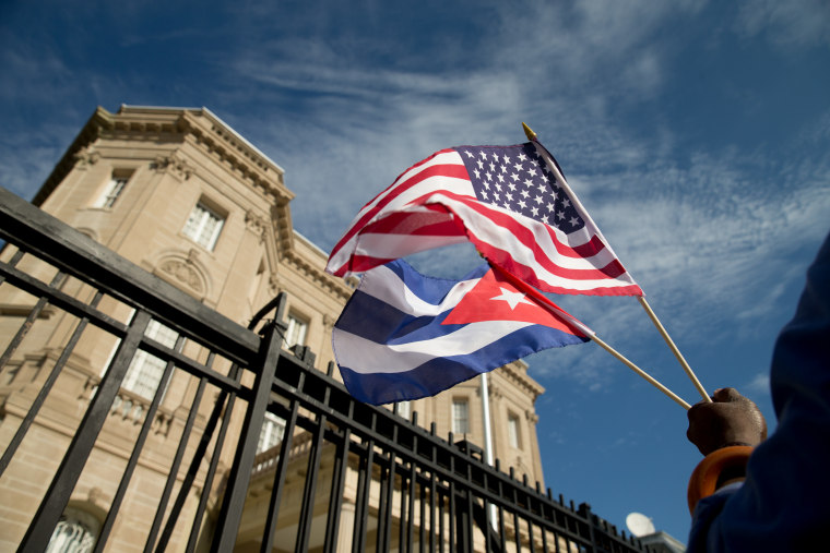 Edwardo Clark, a Cuban-American, holds an American flag and a Cuban flag as he celebrates outside the new Cuban embassy in Washington, Monday, July 20, 2015. The United States and Cuba restored full diplomatic relations Monday after more than five decades of frosty relations rooted in the Cold War.