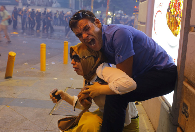 Image: A couple, affected by tear gas used by riot police to disperse demonstrators, reacts in central Istanbul, Turkey,