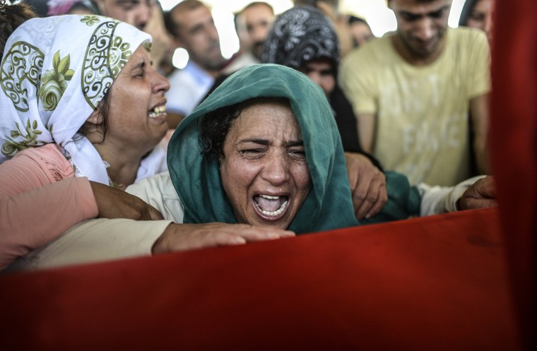 The mother of a victim cries for her son on his coffin during a funeral ceremony in Gaziantep on July 21.