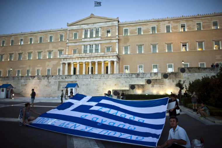 Image: Anti-austerity demonstrators hold up a giant Greek national flag in front of the parliament in Athens, Greece
