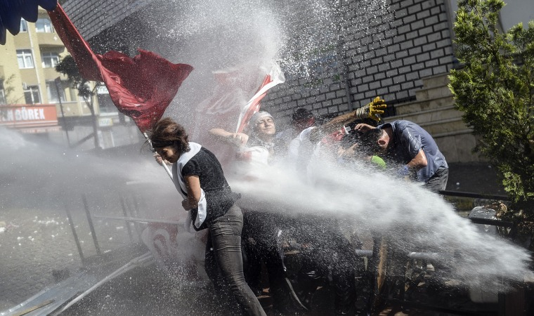 Image: Protesters try to protect themselves as Turkish anti-riot police fire water cannons